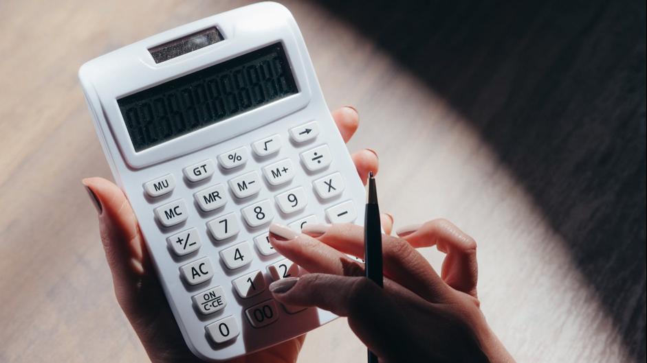 detail ženských rúk pri rátaní na kalkulačke
